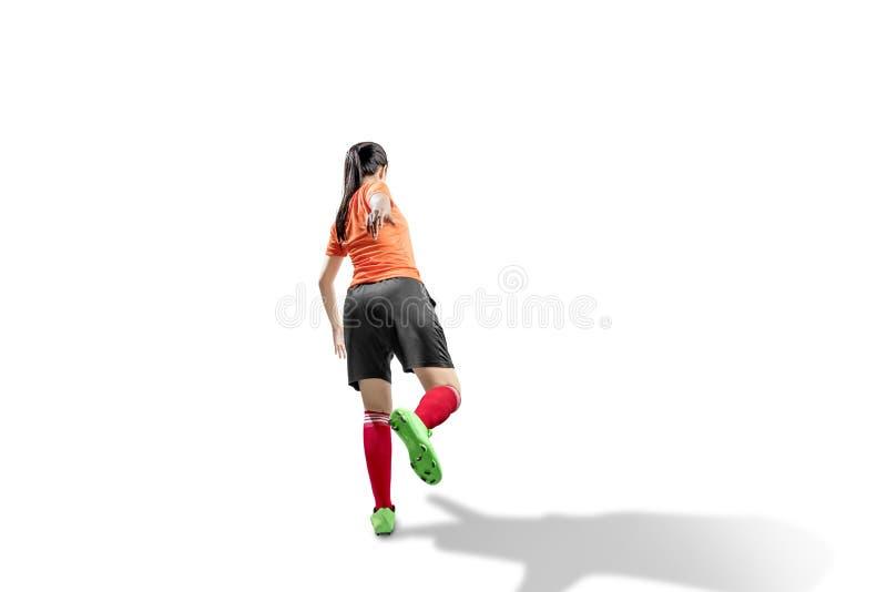 Hinteransicht der asiatischen Fußballspielerin Frau in der Pose, um den Ball zu schlagen stockbilder