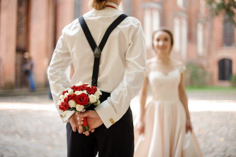 Hintere Ansicht af ein Bräutigam, der einen Heiratsblumenstrauß für seine Braut hält lizenzfreies stockfoto