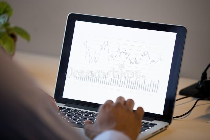 Hintere Ansicht am afrikanischen Geschäftsmann analysieren jährlichen Finanzbericht lizenzfreies stockfoto