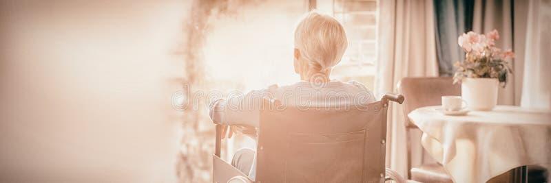 Hintere Ansicht der älteren Frau der älteren Frau, die auf Rollstuhl sitzt stockfoto