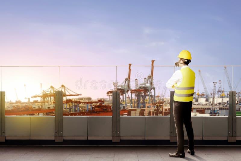 Hintere Ansicht der asiatischen männlichen Arbeitskraft mit Sicherheitswesten-, -Schutzhelm- und -Schutzmaskestellung auf Büroter stockfotos