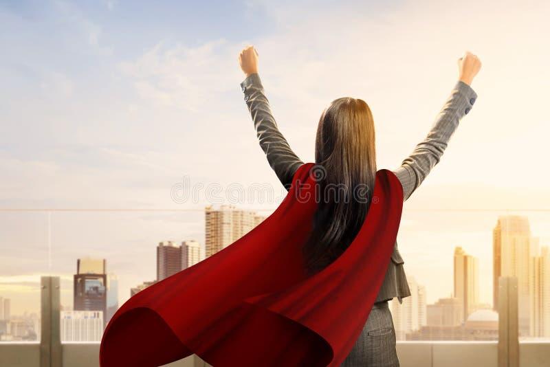 Hintere Ansicht der asiatischen Supergeschäftsfrau mit einem Mantel fühlen sich glücklich stockbilder