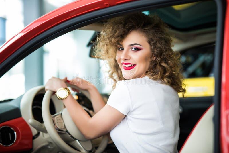 Hintere Ansicht der attraktiven jungen Frau in der Freizeitkleidung, die über ihrer Schulter während Autofahren schaut lizenzfreie stockfotos