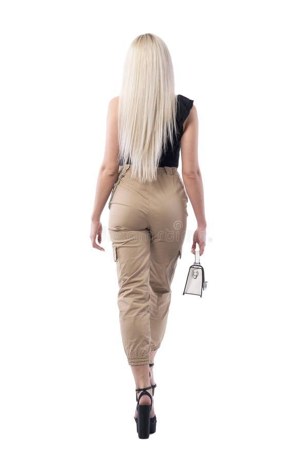Hintere Ansicht der blonden attraktiven Frau, die weg mit kleiner moderner Tasche geht lizenzfreies stockbild