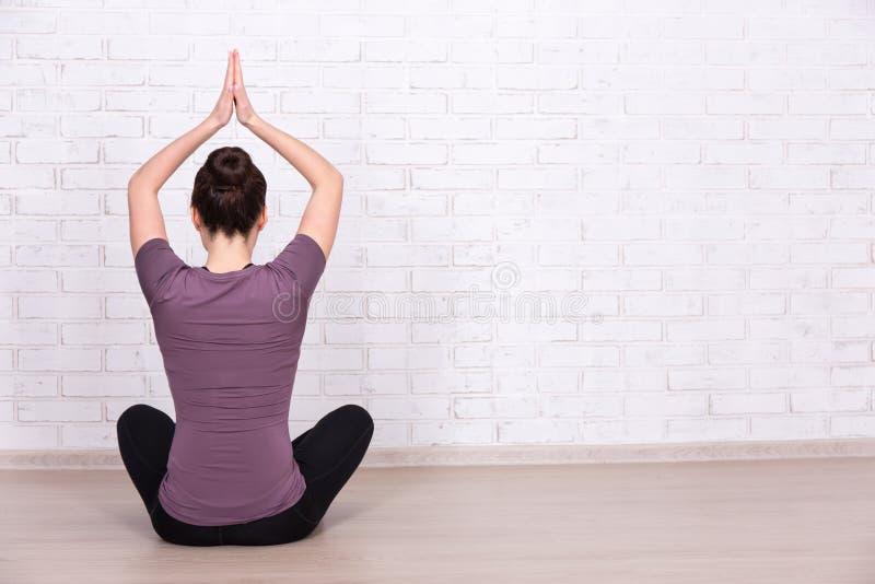 Hintere Ansicht der dünnen sportlichen Frau, die Yoga über weißer Backsteinmauer tut stockbild