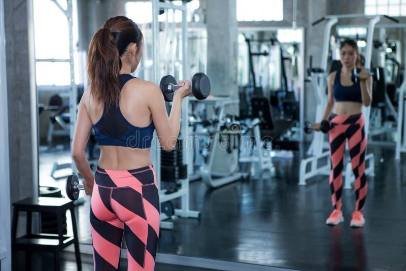 hintere Ansicht der Eignungsfrau ausarbeitend mit Dummköpfen Sportmädchen übt Gewichtheben in der Turnhalle aus, die Spiegel scha stockfotografie