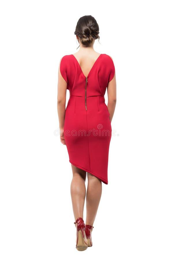 Hintere Ansicht der eleganten Frau mit Brötchenfrisur im roten Abendkleid weg gehend lizenzfreie stockfotos