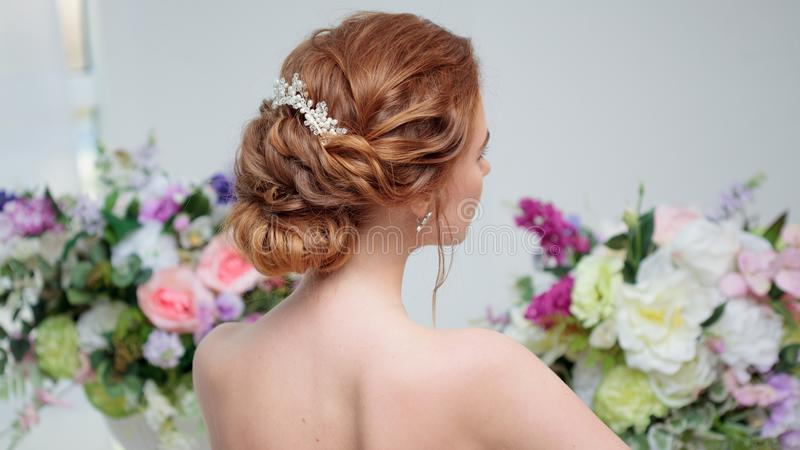 Hintere Ansicht der erstaunlichen jungen Braut Roter Hauptfrauensitz auf dem Stuhl Elegante Frisur lizenzfreies stockfoto