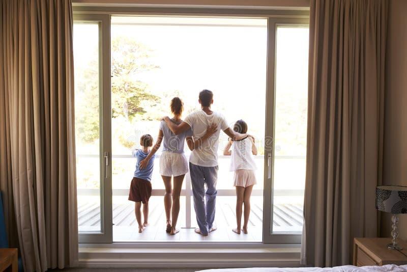 Hintere Ansicht der Familie auf dem Balkon, der heraus am neuen Tag schaut stockbilder