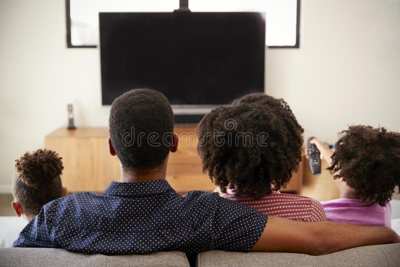 Hintere Ansicht der Familie mit den Kindern, die zusammen im Sofa Watching Fernsehen sitzen lizenzfreies stockfoto