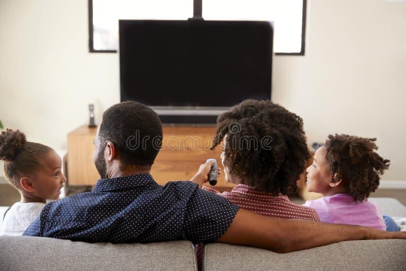 Hintere Ansicht der Familie mit den Kindern, die zusammen im Sofa Watching Fernsehen sitzen lizenzfreie stockfotografie