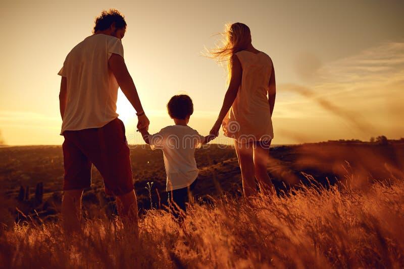 Hintere Ansicht der Familie stehend in der Natur bei Sonnenuntergang stockfotografie