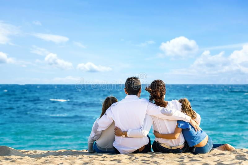 Hintere Ansicht der Familie zusammen sitzend auf dem Strand, der Horizont betrachtet stockfotos