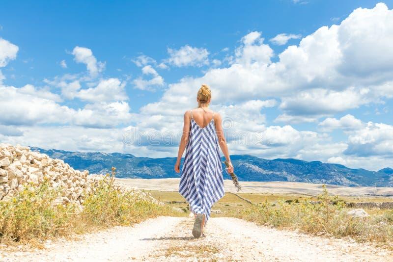 Hintere Ansicht der Frau im Sommerkleiderholdingblumenstrauß von Lavendelblumen beim Gehen im Freien durch trockenes felsiges lizenzfreies stockbild