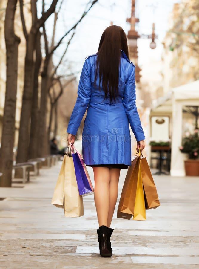 Hintere Ansicht der Frau mit Einkaufstaschen lizenzfreie stockfotografie