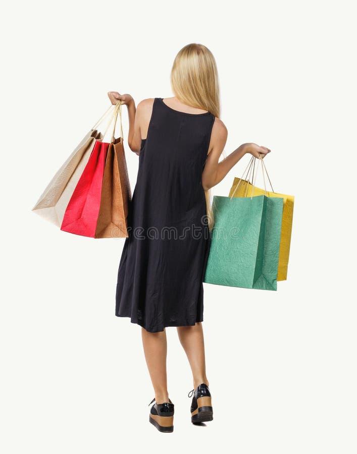 Hintere Ansicht der Frau mit Einkaufstaschen schönes Brunettemädchen in der Bewegung Rückseitenperson lizenzfreie stockfotos