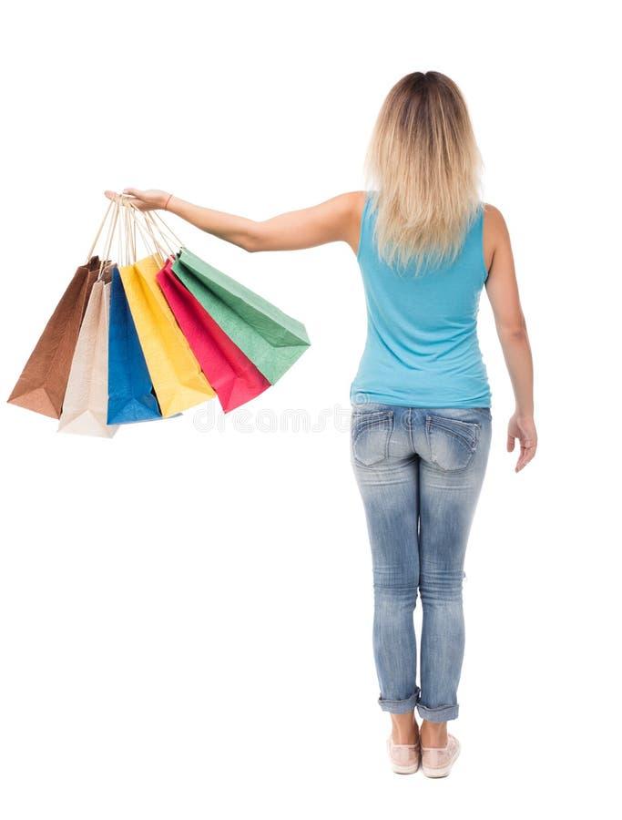 Hintere Ansicht der Frau mit Einkaufstaschen schönes Brunettemädchen in der Bewegung Rückseitenperson lizenzfreies stockbild