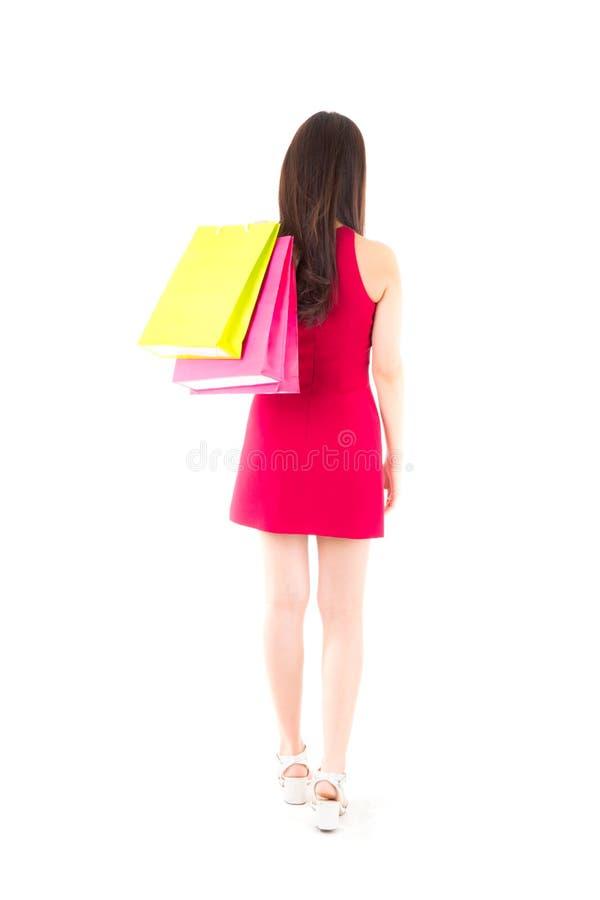 Hintere Ansicht der Frau mit Einkaufstaschen schönes Mädchen im roten Kleid, das Papiertüte hält stockbild