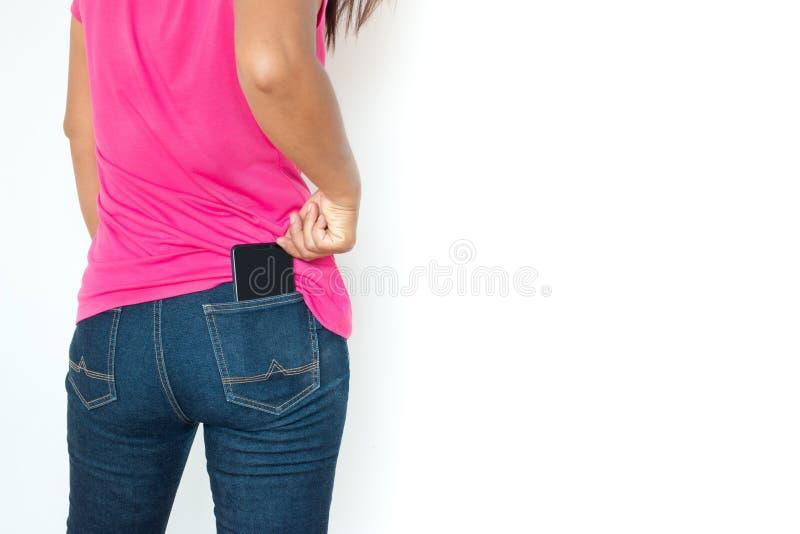 Hintere Ansicht der Frau mit Smartphone in den Jeans R?ckseitenansicht der Person Lokalisiert ?ber wei?em Hintergrund stockbild