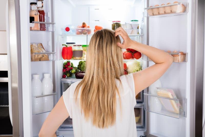 Hintere Ansicht der Frau schauend im Kühlschrank stockfotografie