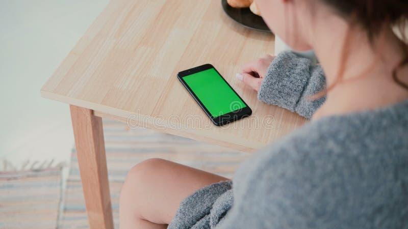 Hintere Ansicht der Frau zu Hause sitzend am Tisch in der Küche Brunettemädchen benutzt Smartphone, grünen Schirm lizenzfreie stockbilder