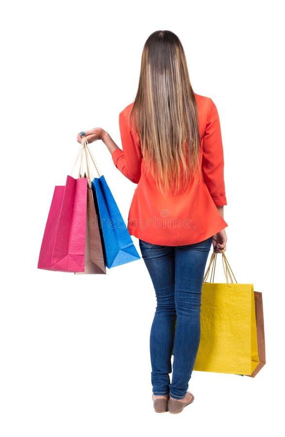 Hintere Ansicht der gehenden Frau in der Jeansfrau mit Einkaufstaschen stockfoto