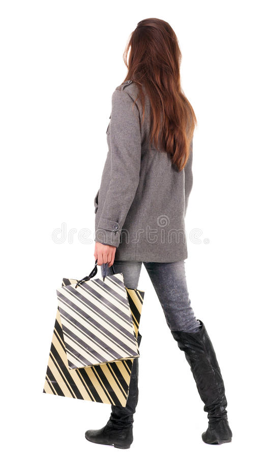Hintere Ansicht der gehenden Frau in der Mantelfrau mit Einkaufstaschen. stockfoto