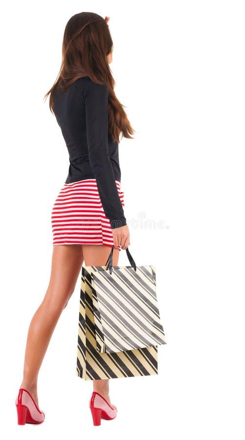 Hintere Ansicht der gehenden Frau im Kleid mit Einkaufstaschen. stockbilder