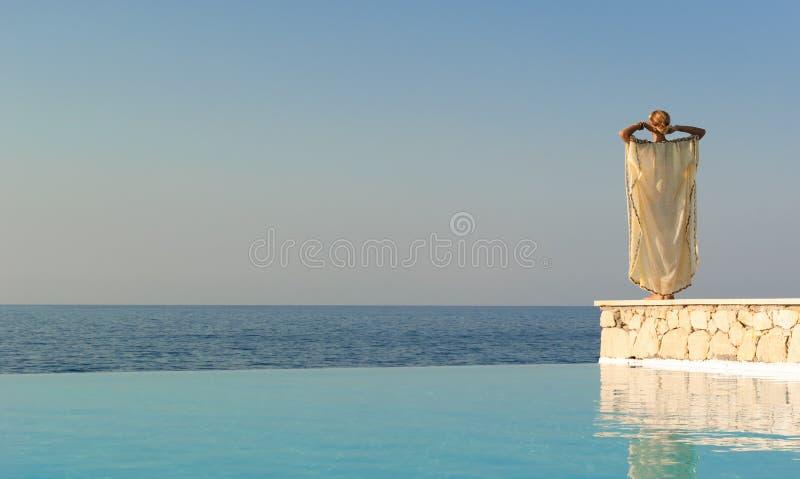 Hintere Ansicht der griechischen Artfrau nahe Unbegrenztheitspool lizenzfreies stockfoto
