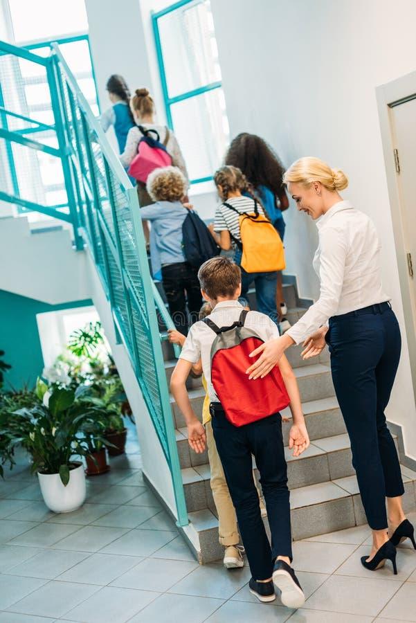 hintere Ansicht der Gruppe der Schüler und des Lehrers, die oben gehen stockfotografie