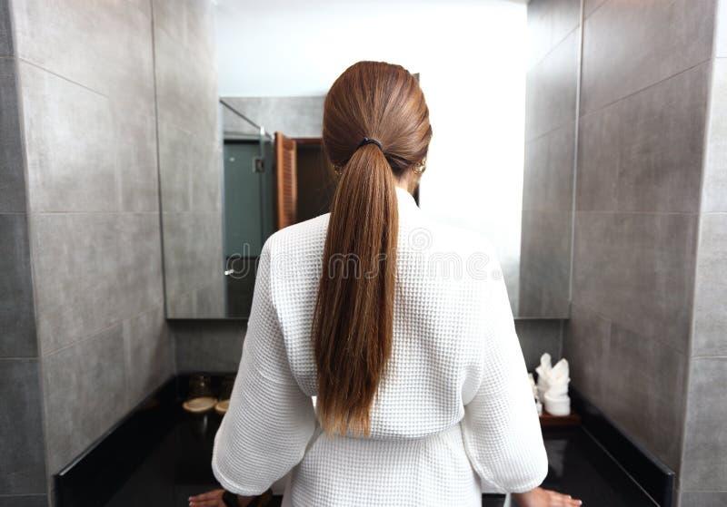 Hintere Ansicht der hübschen jungen Frau wickelte Haar ein lizenzfreie stockfotos