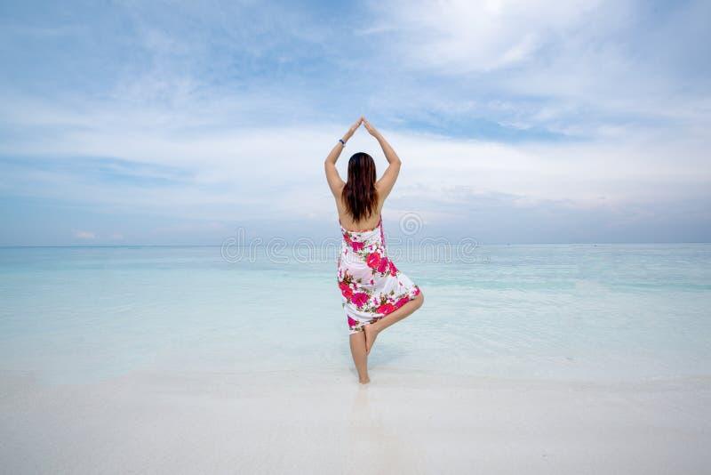 Hintere Ansicht der herrlichen Frau in der Yogahaltung auf dem Strand auf einem sonnigen stockbilder