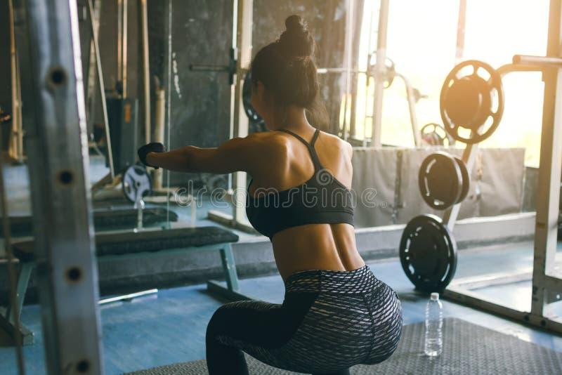 Hintere Ansicht der jungen asiatischen Frau in der Sportkleidung, die Hocke am Fitnessstudio tut stockfotos
