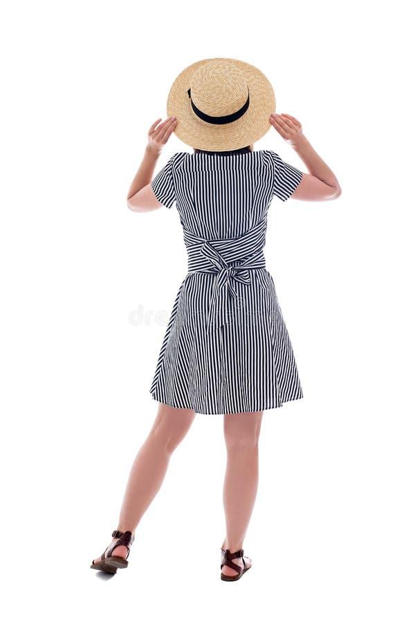 Hintere Ansicht der jungen Frau in gestreiftem Kleid und im Strohhut lokalisiert auf Weiß lizenzfreies stockfoto