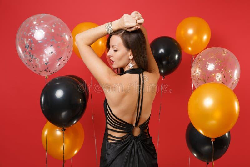 Hintere hintere Ansicht der jungen Frau im schwarzen Kleid feiernd, steigende Hände, beiseite schauend auf heller roter Hintergru lizenzfreie stockfotos