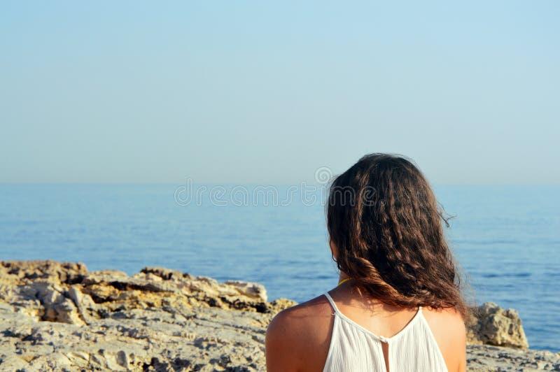 Hintere Ansicht der jungen Frau mit dem gelockten Haar, welches das Meer von felsigem Küste Reisendem auf Hintergrundstrand betra stockfotos