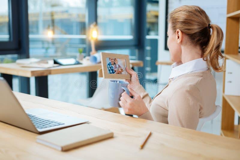 Hintere Ansicht der jungen Frau mit einem Foto lizenzfreie stockfotografie
