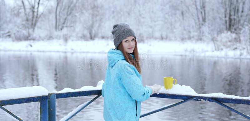 Hintere Ansicht der jungen Frau mit einer Schale heißem Tee oder Kaffee auf Ufer des verschneiten Winters stockfotos