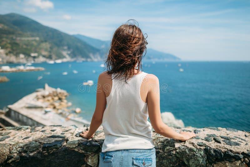 Hintere Ansicht der jungen Frau schönen Meerblick in Italien genießend lizenzfreie stockfotos