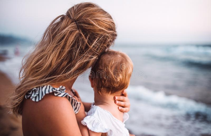 Hintere Ansicht der jungen Mutter mit einem Kleinkindmädchen auf Strand an den Sommerferien stockfotografie