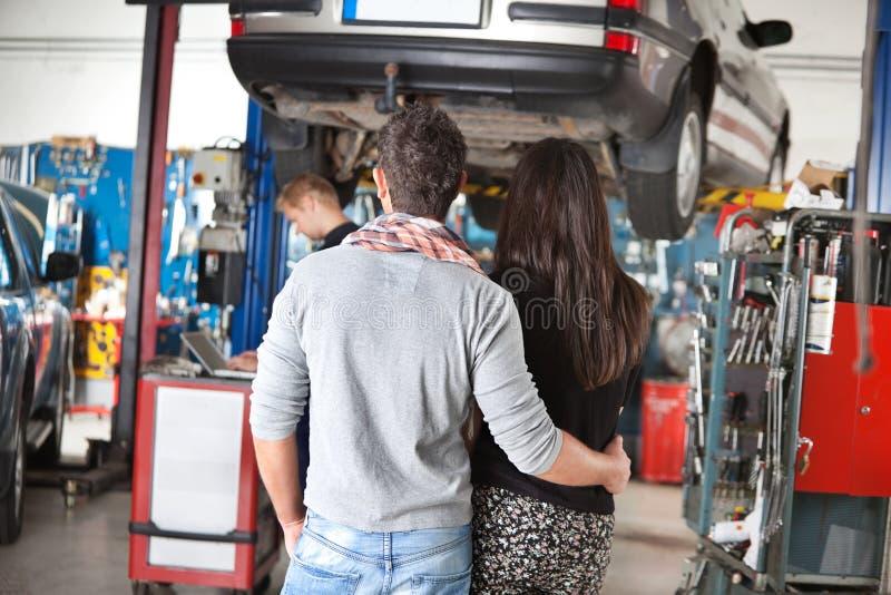Hintere Ansicht der jungen Paare in der Garage stockfotos