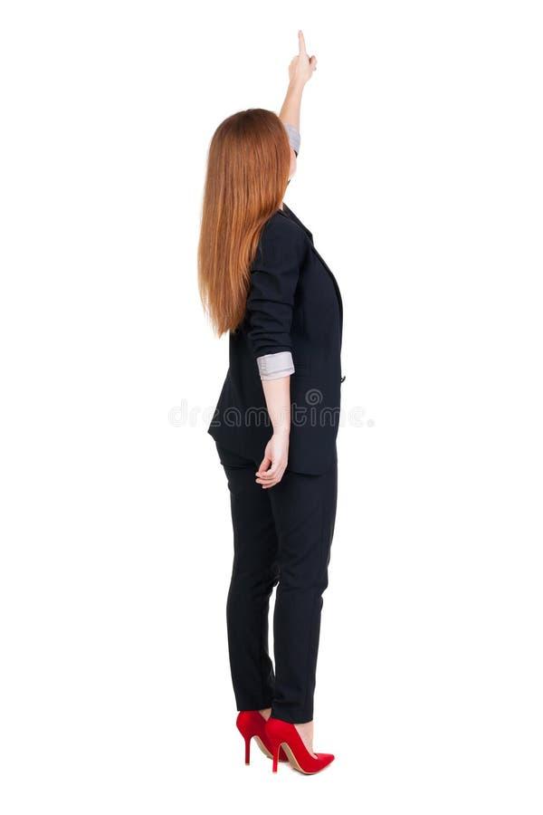 Hintere Ansicht der jungen RothaarigeGeschäftsfrau, die auf wal zeigt stockbilder