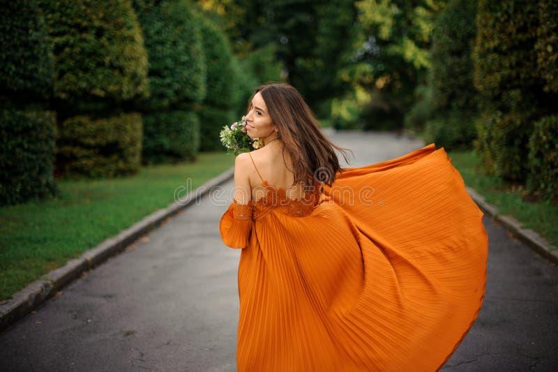 Hintere Ansicht der jungen und attraktiven Frau im langen orange Kleid stockfotografie