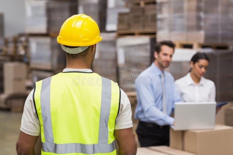 Hintere Ansicht der Lagerarbeitskraft vor seinen Managern stockbild