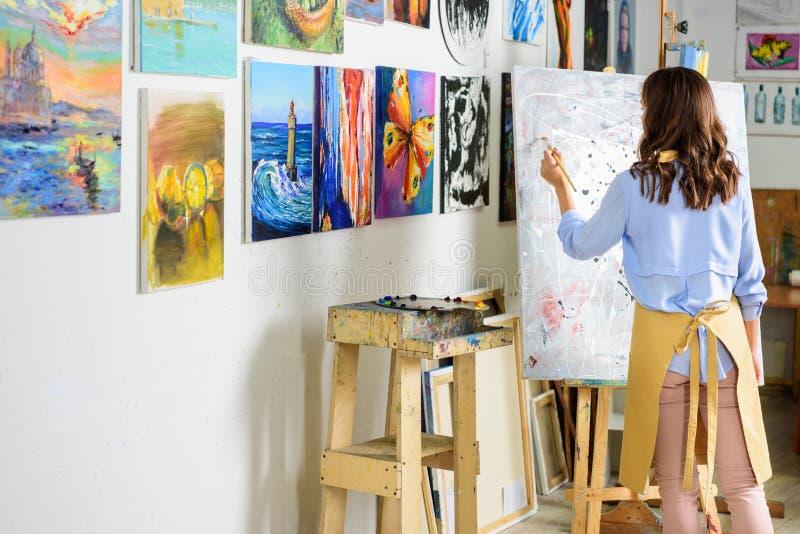 hintere Ansicht der linkshändigen weiblichen Künstlermalerei auf Segeltuch lizenzfreies stockbild