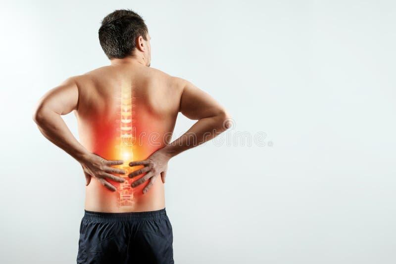 Hintere Ansicht, der Mann hält seine Hände hinter seiner Rückseite, Schmerz in der Rückseite, Schmerz im Dorn, hervorgehoben im R stockfotografie