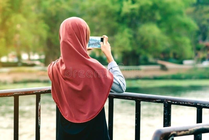 Hintere Ansicht der moslemischen Frau entspannen sich und bewundern die schöne Landschaft am Abend auf der Brücke des Flusses Kwa stockbild