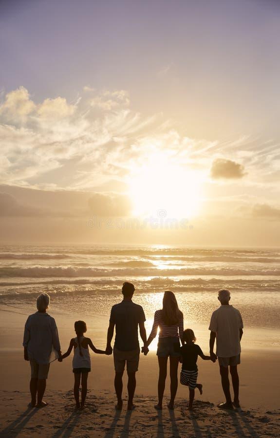 Hintere Ansicht der multi Generations-Familie silhouettiert auf Strand stockfotografie