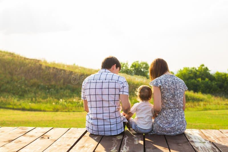 Hintere Ansicht der Mutter, des Vaters und des Sohns, die zusammen draußen sitzen stockfotos