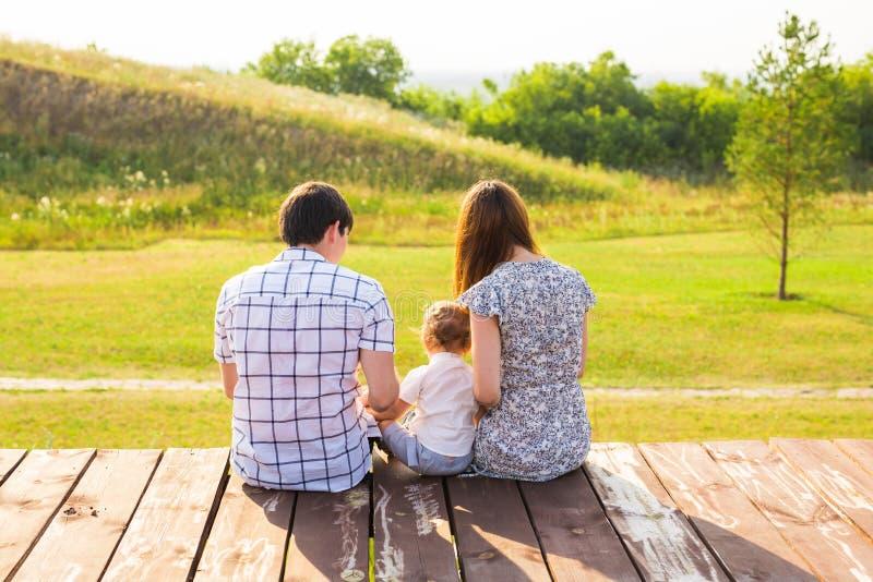 Hintere Ansicht der Mutter, des Vaters und des Sohns, die zusammen draußen sitzen lizenzfreie stockfotos
